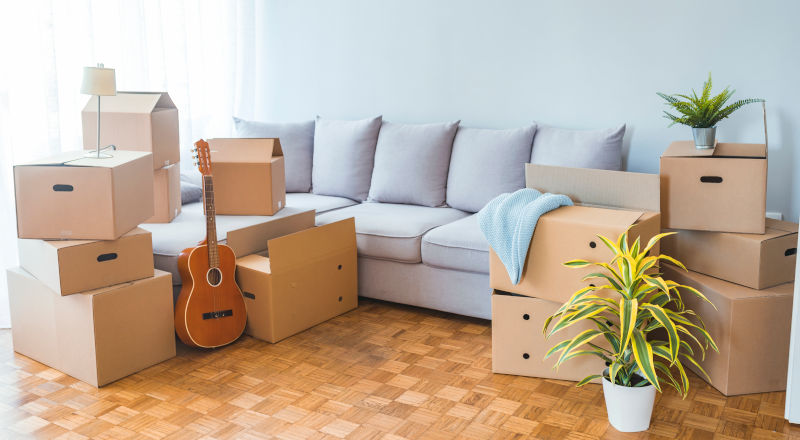 Boxes for moving next to a sofa and a guitar