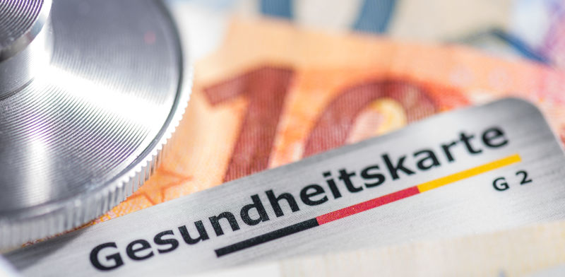 A German health insurance card and a 10.- Euro bill
