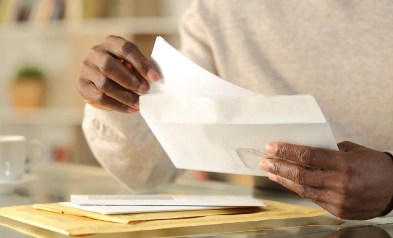A person putting a letter in an envelope