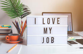 A card on a table saying I love my job with computer in the background