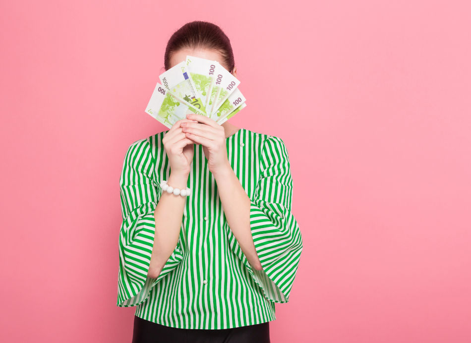 A woman hiding behind banknotes