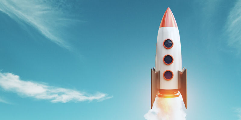 A painted toy rocket starting in front of a blue sky